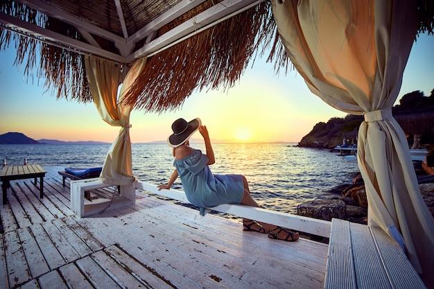 Donna con cappello rilassante in riva al mare in un lussuoso resort sulla spiaggia al tramonto godendo la vacanza al mare perfetta vacanza a bodrum, in turchia. concetto di viaggio di estate di vista sul mare all'aperto Foto Premium