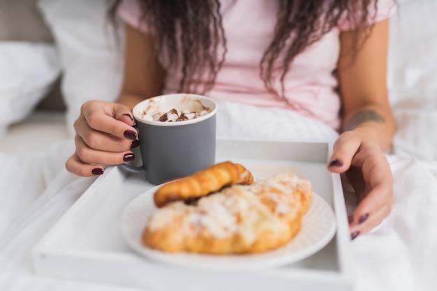 La donna fa colazione a letto in un appartamento luminoso oa casa. finestra luce ritratto ragazza giovane mangiare croissant e bere caffè. Foto Premium