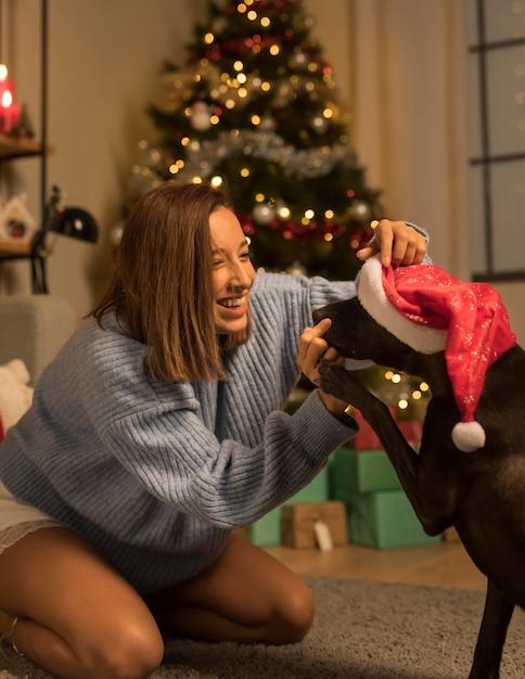 Donna che si diverte a natale con il suo cane che indossa il cappello della santa Foto Premium