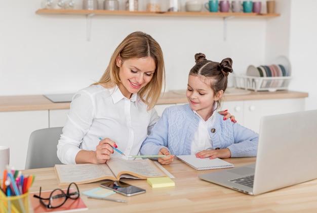 Donna che aiuta sua figlia a fare i compiti a casa Foto Premium