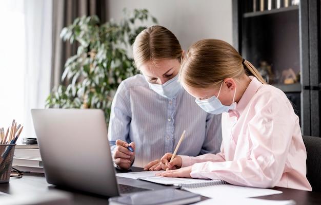 Donna d'aiuto della ragazza con i compiti mentre indossa una maschera medica Foto Premium