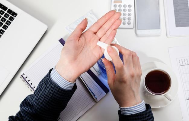 Una donna alla sua scrivania tratta le sue mani con gel antibatterico. donna di affari nel luogo di lavoro con maschera antisettica e protettiva. Foto Premium