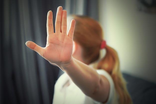 La donna nasconde il suo viso a portata di mano. donna che tiene la mano tesa verso la telecamera, coprendosi il viso, evitando di essere vista o fermando un problema Foto Premium