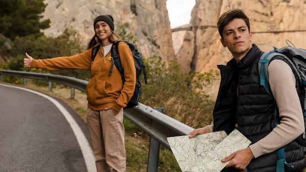 Donna autostop per una macchina e uomo con mappa Foto Premium