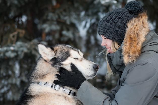 Donna che mantiene alaskan malamute faccia con gli occhi chiusi dal piacere in inverno Foto Premium