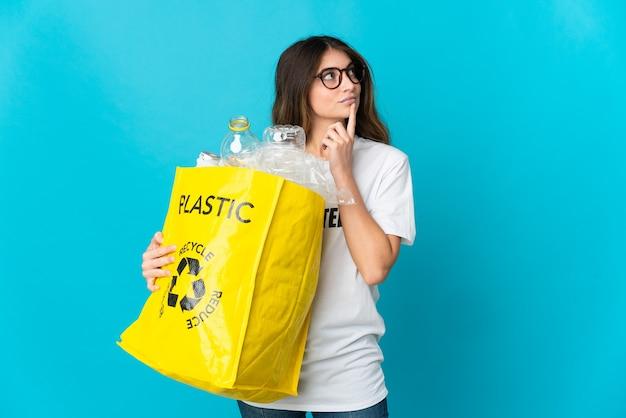 Donna che tiene una borsa piena di bottiglie da riciclare isolato sull'azzurro che ha dubbi mentre osserva in su Foto Premium