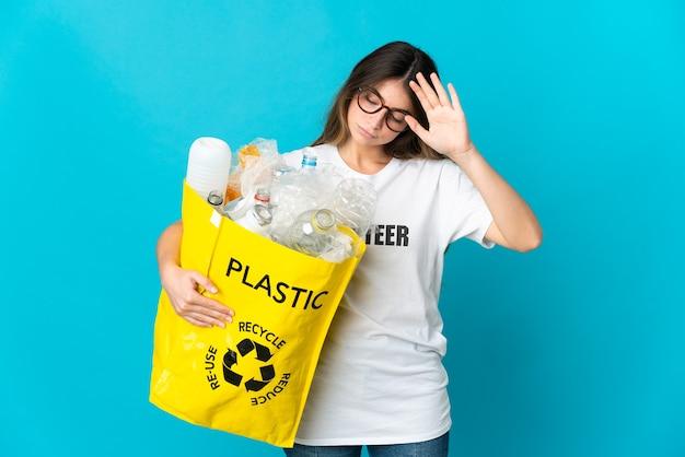 Donna che tiene una borsa piena di bottiglie da riciclare isolato su blu facendo gesto di arresto e deluso Foto Premium