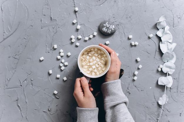 Donna che tiene tazza di caffè caldo, foto del primo piano delle mani in maglione caldo con la tazza, concetto di mattina di inverno, vista dall'alto Foto Premium