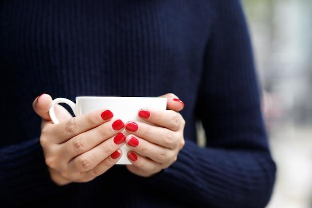 Una donna con una tazza di caffè caldo al bar Foto Premium