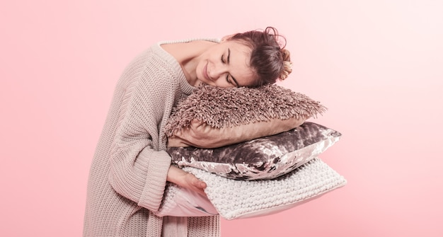 Donna che tiene tre cuscini moderni per il sofà, parete rosa nella tendenza, concetto domestico accogliente pulito di minimalismo Foto Premium