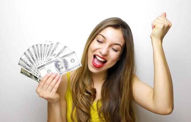 Donna che tiene le banconote dei soldi e che celebra Foto Premium