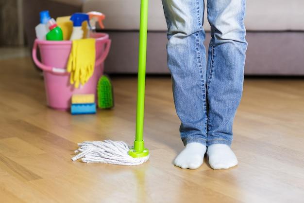 Donna che mantiene mop a casa Foto Premium