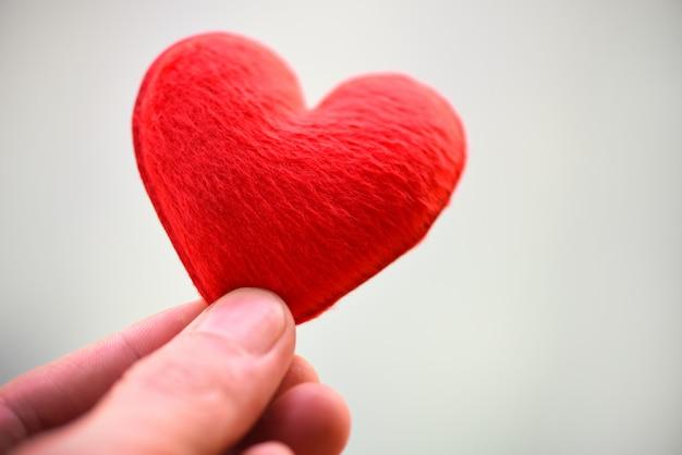 La donna che tiene il cuore rosa in mano per il giorno di san valentino o donare aiuto dare amore calore prendersi cura - cuore a portata di mano per il concetto di filantropia Foto Premium