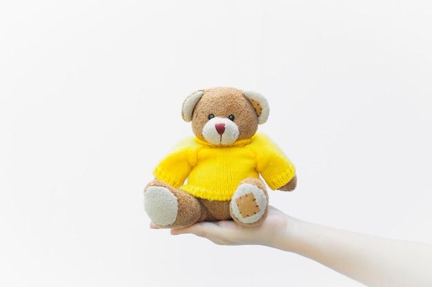 La holding della donna e la protezione danno un giocattolo marrone dell'orsacchiotto indossare camicie gialle che si siedono sul primo piano bianco del fondo, simbolo dell'amore o della datazione Foto Premium