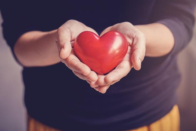 Donna che mantiene cuore rosso, assicurazione sanitaria, donazione, concetto di volontariato di beneficenza Foto Premium