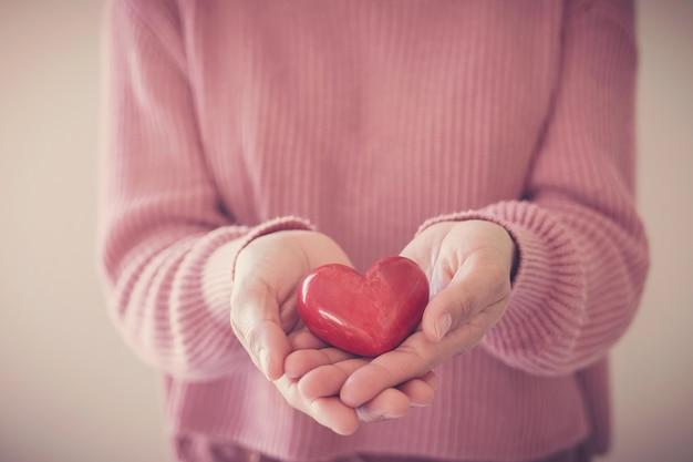 Donna che tiene cuore rosso, assicurazione sanitaria, concetto di donazione, giornata mondiale della salute mentale, giornata mondiale del cuore Foto Premium