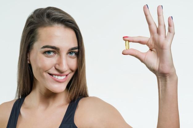 La donna tiene la capsula con vitamina e, olio di pesce Foto Premium