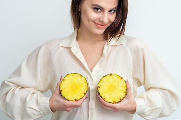 La donna tiene due metà dell'ananas. concetto di ghiandole mammarie sane e bellezza della pelle. Foto Premium