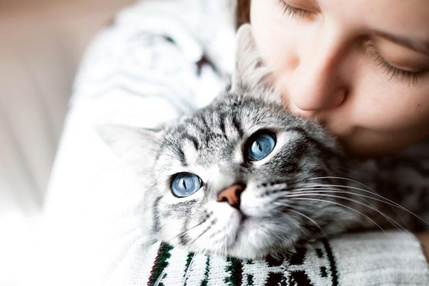 Donna a casa che bacia il suo gatto lanuginoso adorabile Foto Premium