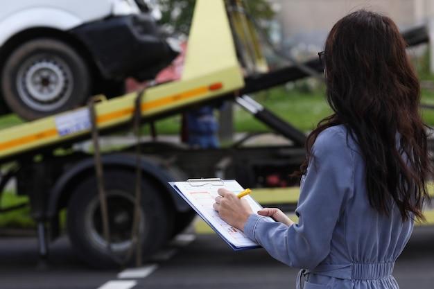 L'agente di assicurazione donna prepara i documenti per l'auto che viene portata via dal carro attrezzi Foto Premium