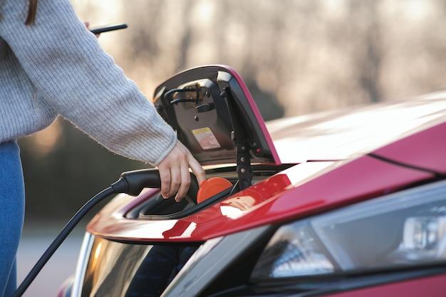 La donna sta tappando il veicolo elettrico per caricare la batteria dell'auto al parcheggio. avvicinamento. veicolo elettrico con cavo di ricarica collegato, parcheggio per veicoli elettrici, cavo per caricabatterie, stazione di ricarica, futuro sostenibile. Foto Premium