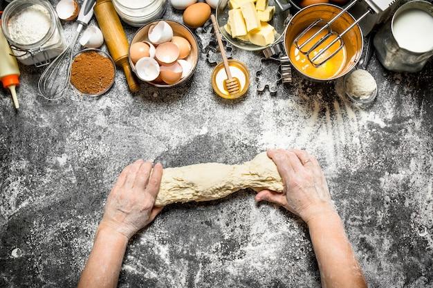 La donna impasta la pasta con vari ingredienti sul tavolo Foto Premium