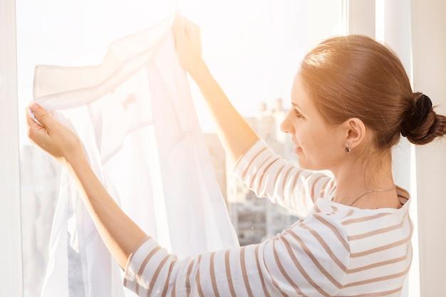Donna che guarda i vestiti puliti Foto Premium