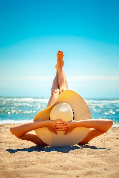 Donna sdraiata sulla spiaggia Foto Premium