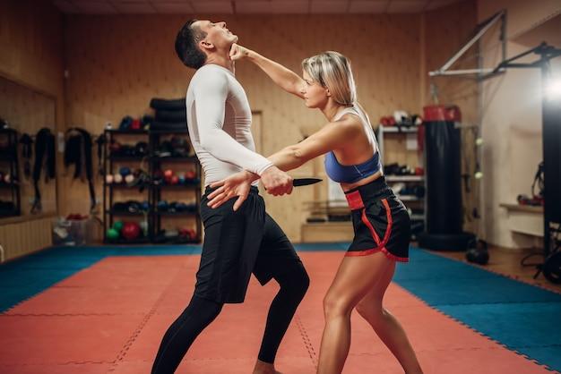 La donna fa un pugno alla gola, allenamento di autodifesa con personal trainer maschile, interno della palestra. persona di sesso femminile in formazione, pratica di autodifesa Foto Premium