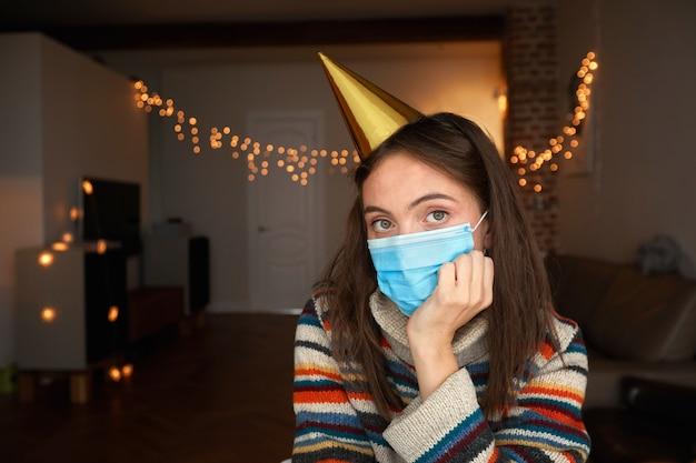Donna in maschera e cappello da festa si siede in una stanza buia con luci e tiene la testa in mano a casa Foto Premium