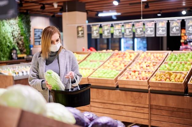 La donna in maschere mediche sta facendo la spesa in drogheria durante la pandemia di virus Foto Premium