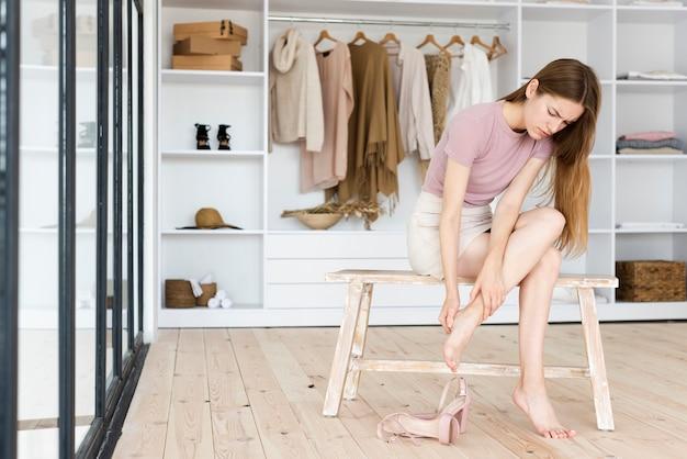 Donna di messaggistica i suoi piedi dopo aver indossato i tacchi alti Foto Premium