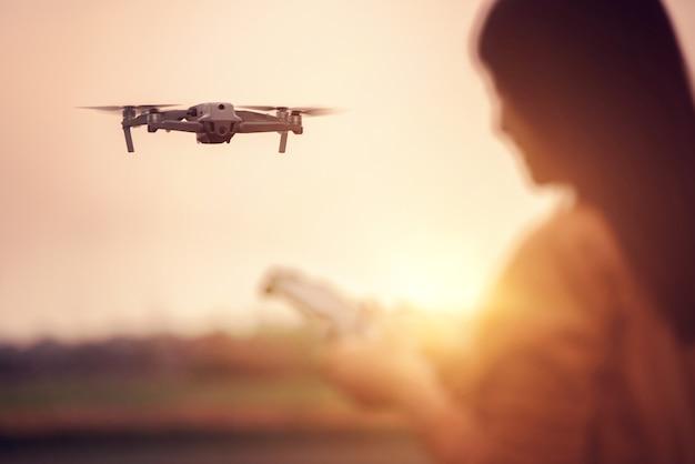 Donna che fa funzionare un drone con telecomando. Foto Premium