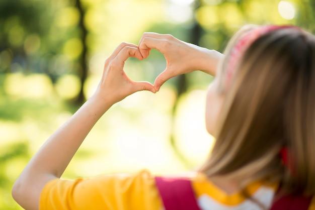 Donna all'aperto che fa un cuore con le mani Foto Premium