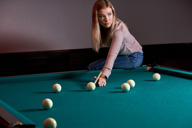 Donna che gioca a biliardo, preparandosi mirando a sparare palle da biliardo su un tavolo da biliardo, seduto su di esso Foto Premium
