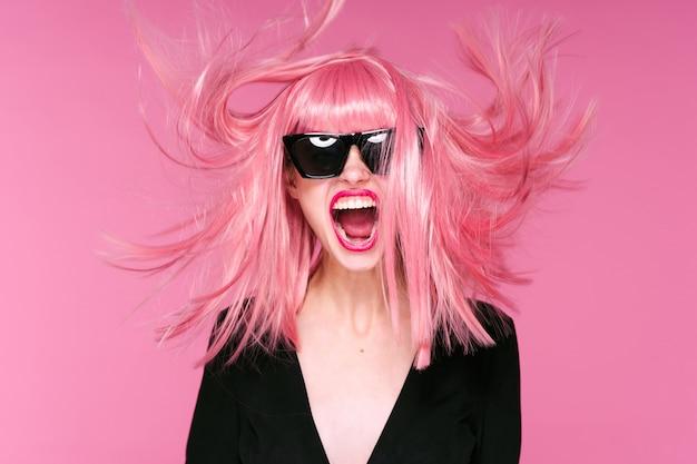 Ritratto di donna capelli rosa, parete rosa, occhiali e accessori Foto Premium