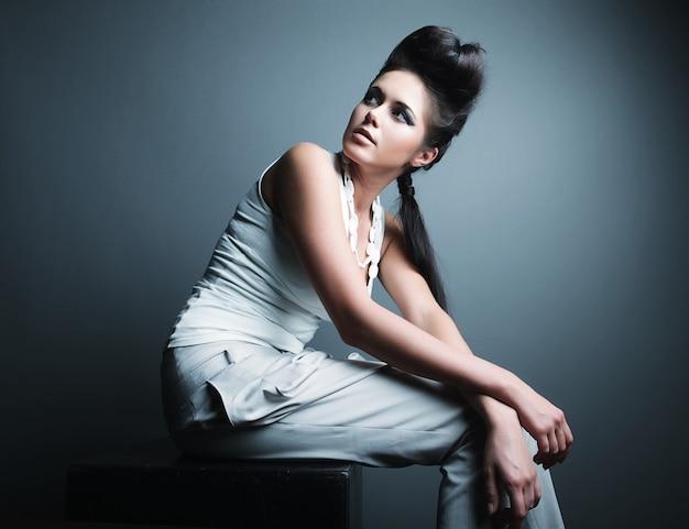 Donna in posa su grigio Foto Premium