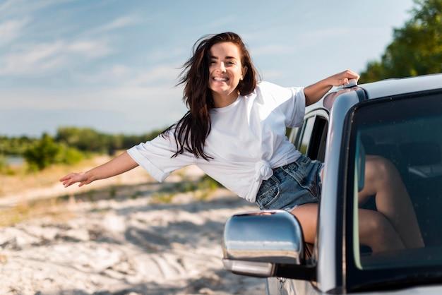 Donna in posa mentre si appoggia sul finestrino della macchina Foto Premium