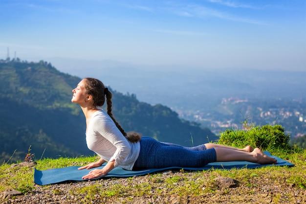 La donna pratica la posa della cobra di asana bhujangasana di yoga Foto Premium