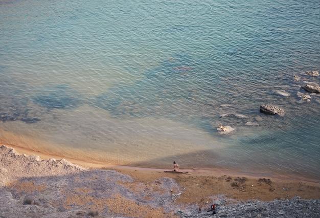 Donna che pratica yoga sulla spiaggia Foto Premium