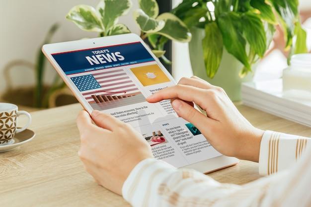 Donna che legge notizie online sul suo tablet dal soggiorno Foto Premium