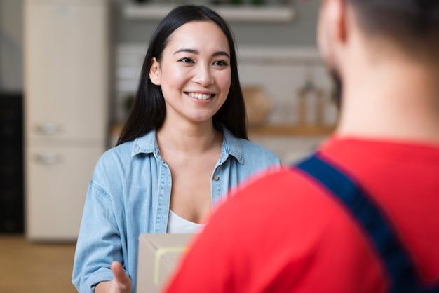Donna che riceve il suo ordine online dal fattorino Foto Premium