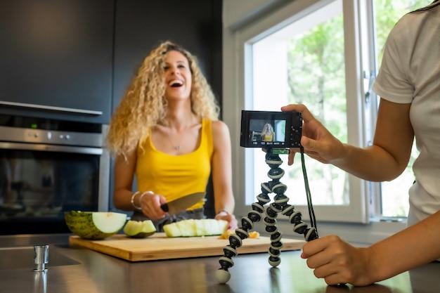 La registrazione della donna con una macchina fotografica gradisce una taglierina del melone in una cucina Foto Premium
