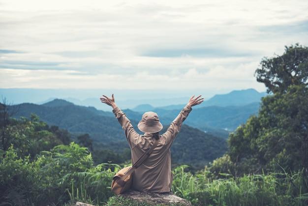 Donna che si distende con le braccia alzate sulla cima della montagna. Foto Premium