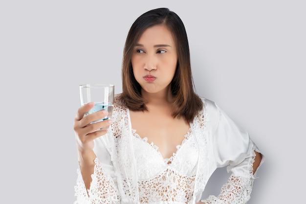 La donna si sciacqua la bocca con un collutorio dopo essersi lavata i denti dopo essersi svegliata per iniziare la giornata. Foto Premium