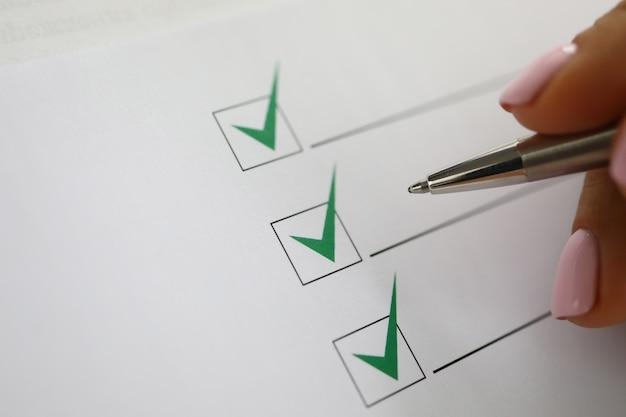 La mano della donna tiene la penna e segna i segni di spunta verdi nel documento. Foto Premium
