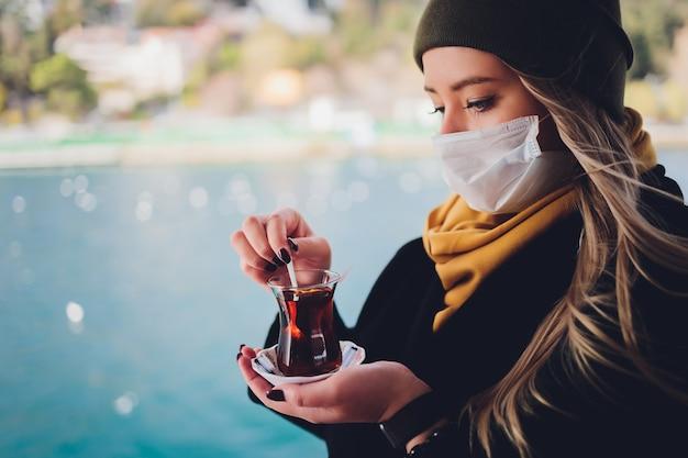 La mano di una donna è in possesso di una tazza bianca di bevanda calda a base di latte con cannella chiamato turco salep sahlep sullo sfondo di acqua increspata e nebbiosa torre della fanciulla in lontananza, istanbul Foto Premium
