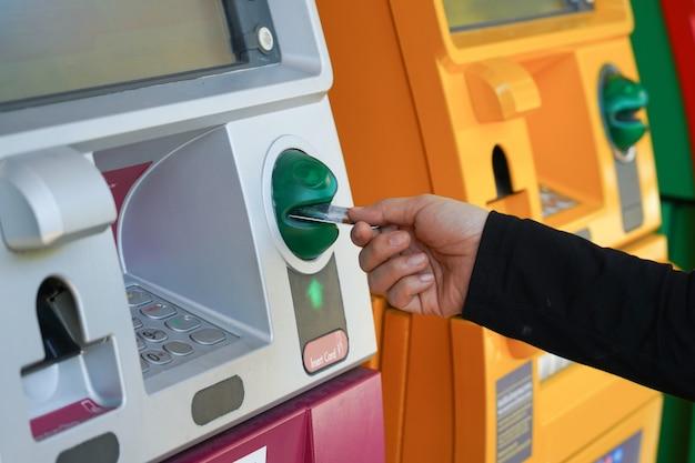 Mano della donna che utilizza la carta di credito per prelevare o trasferire denaro dal bancomat. Foto Premium