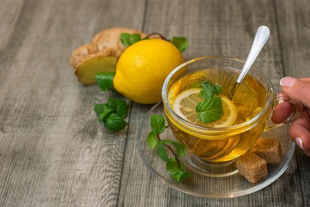 La mano della donna con la tazza di tè allo zenzero, zucchero bruno lemonnd su legno grigio Foto Premium