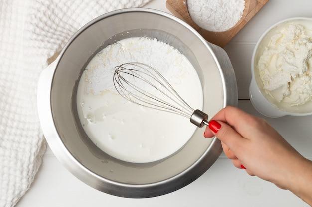 Una mano di donna con una frusta sopra una ciotola di panna montata e zucchero a velo vicino a un asciugamano e ciotole di zucchero a velo e ricotta. lay piatto. Foto Premium